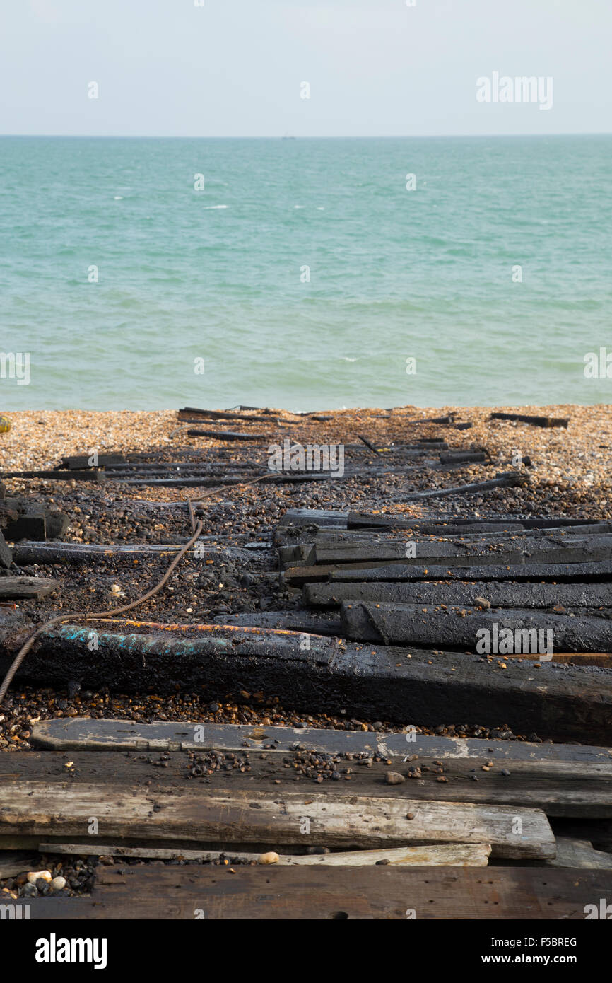 Beach scene involving tarred and oiled wooden planks used for boat launching - Stock Image