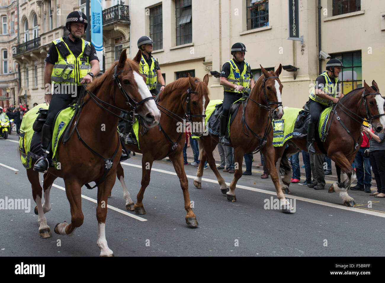 Mounted police officers riding horses during a Wales rugby game. - Stock Image