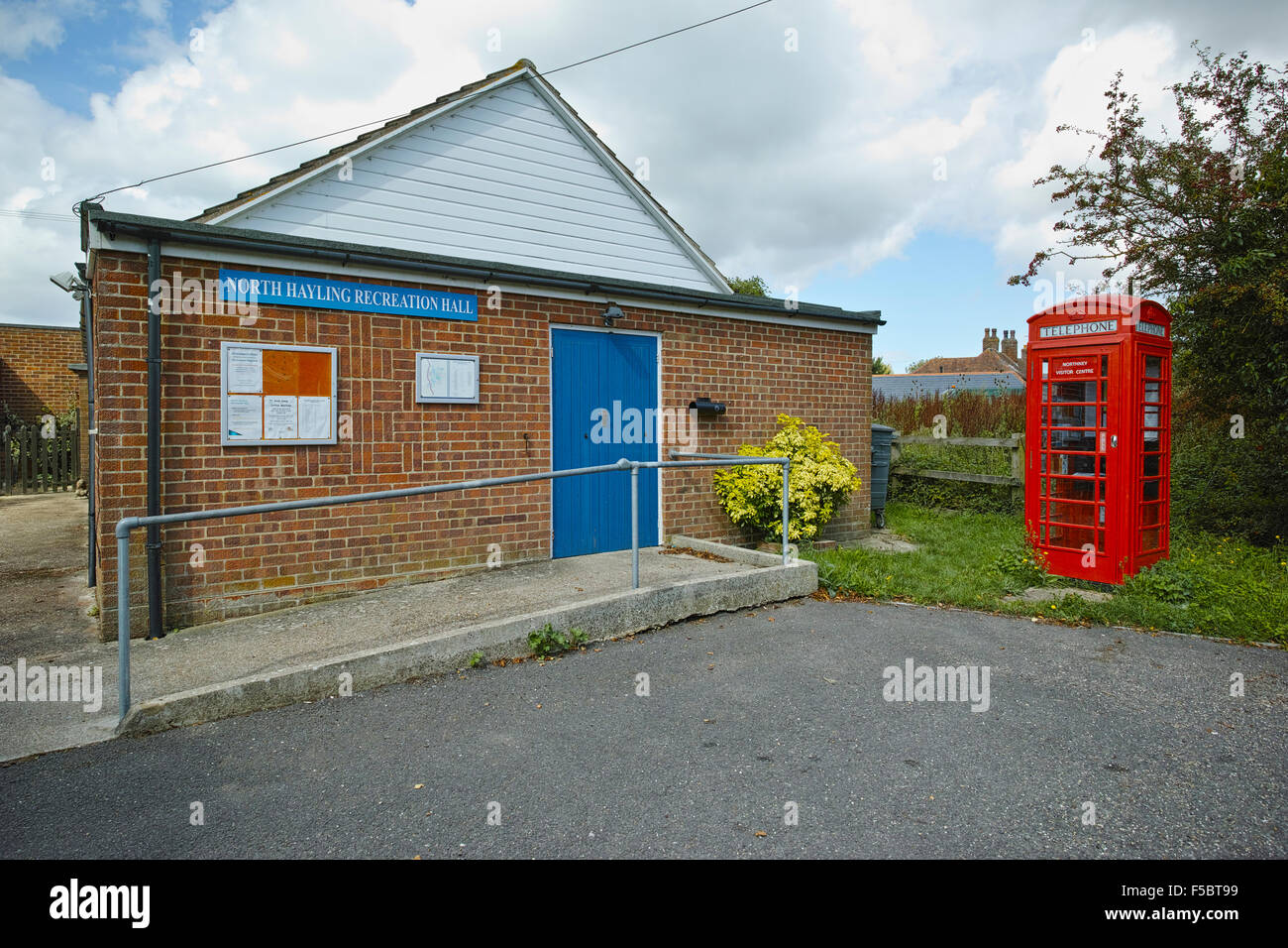 Village hall with red telephone kiosk tourist information centre showing the important of places to meet in rural - Stock Image