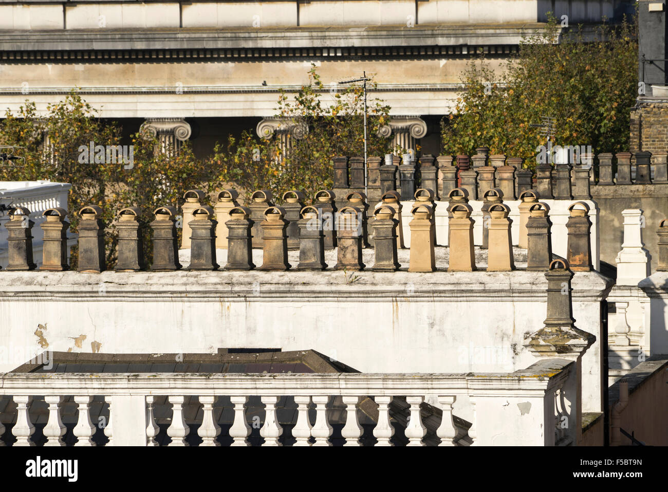 Chimneys and rooftops of Bloomsbury London with columns of the British Museum in the bacground - Stock Image