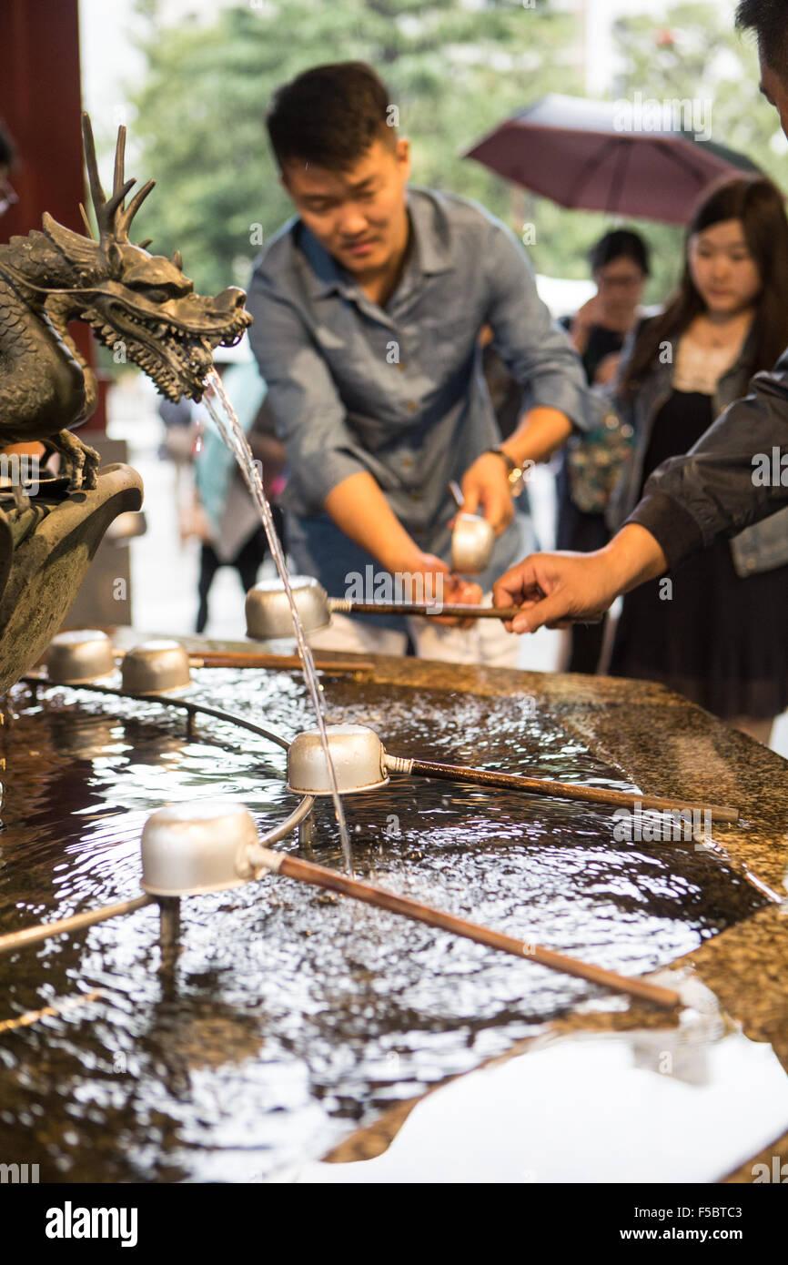Man washing hands at fountain - Stock Image