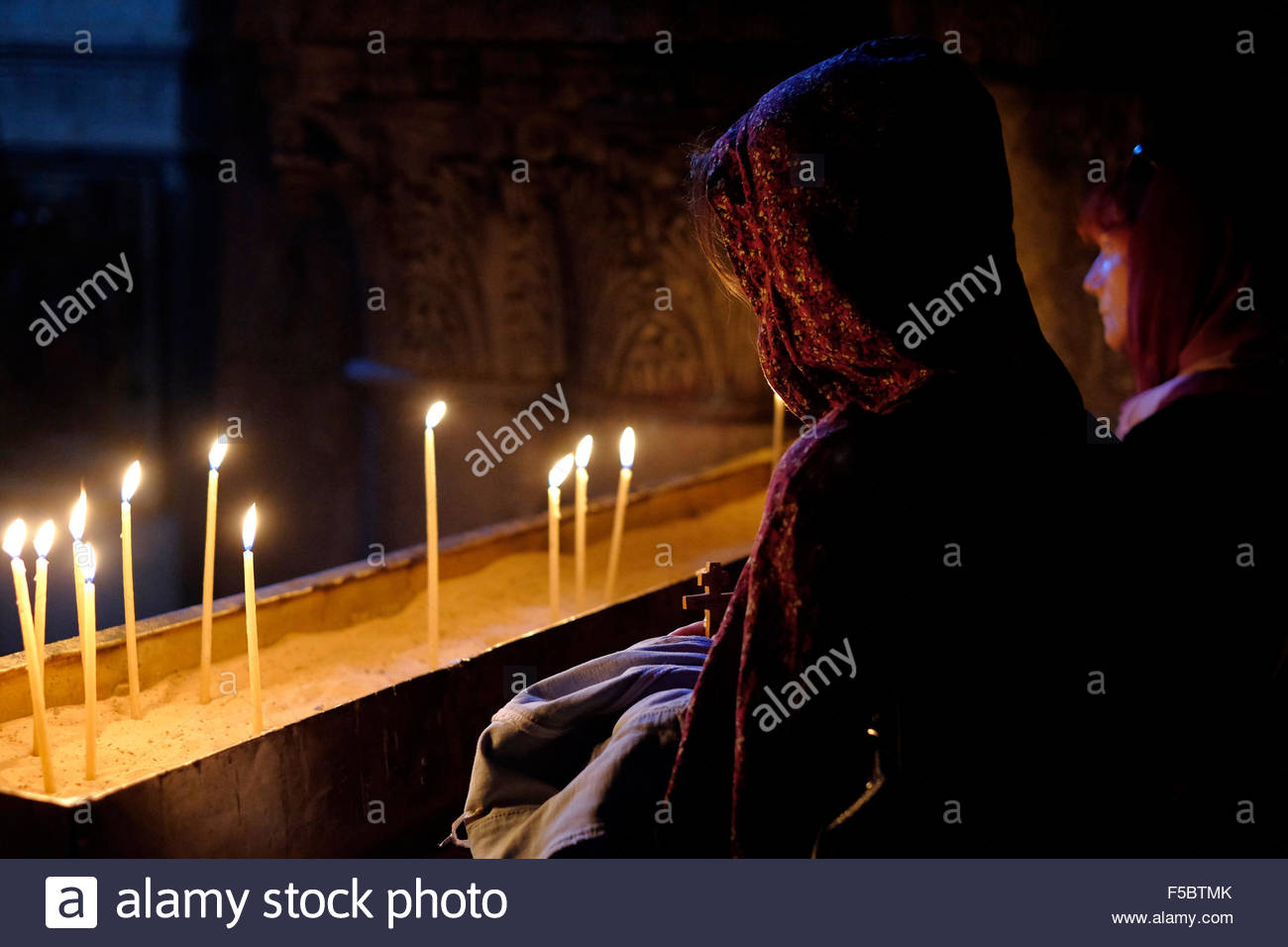 Christian worshipers lighting candles inside Church of Holy Sepulchre in the Old city Jerusalem Israel - Stock Image