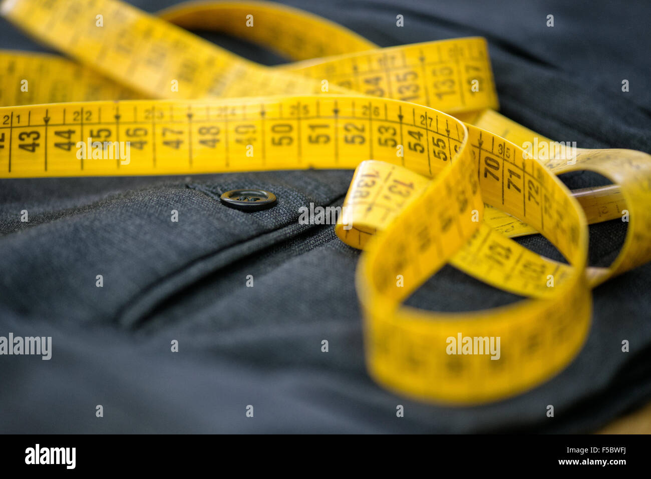 Measuring tape on pants in a tailor workshop, closeup - Stock Image