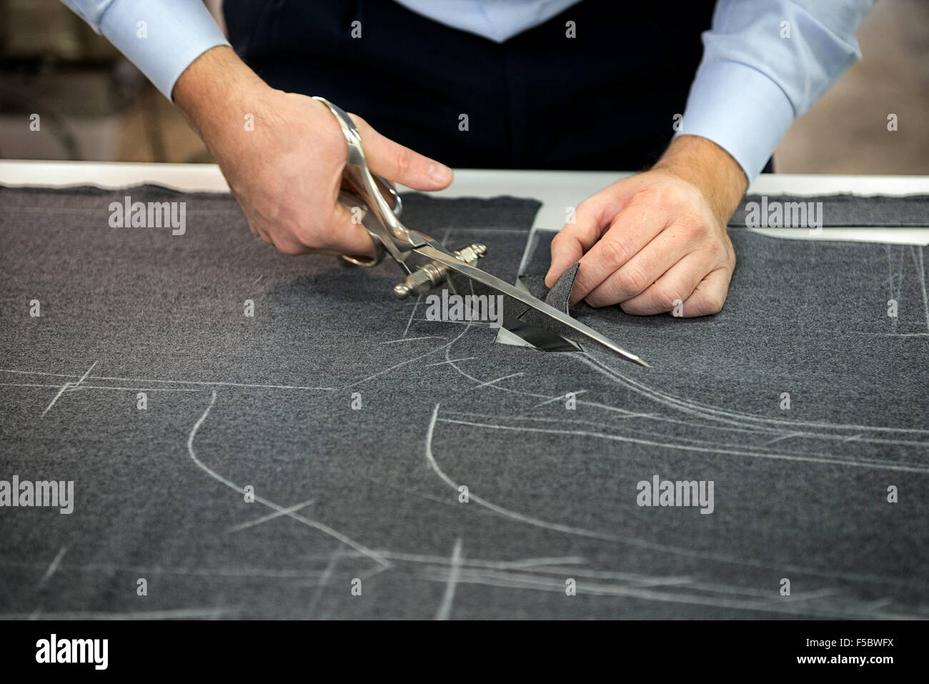 Tailor cutting fabric using large scissors or shears - Stock Image
