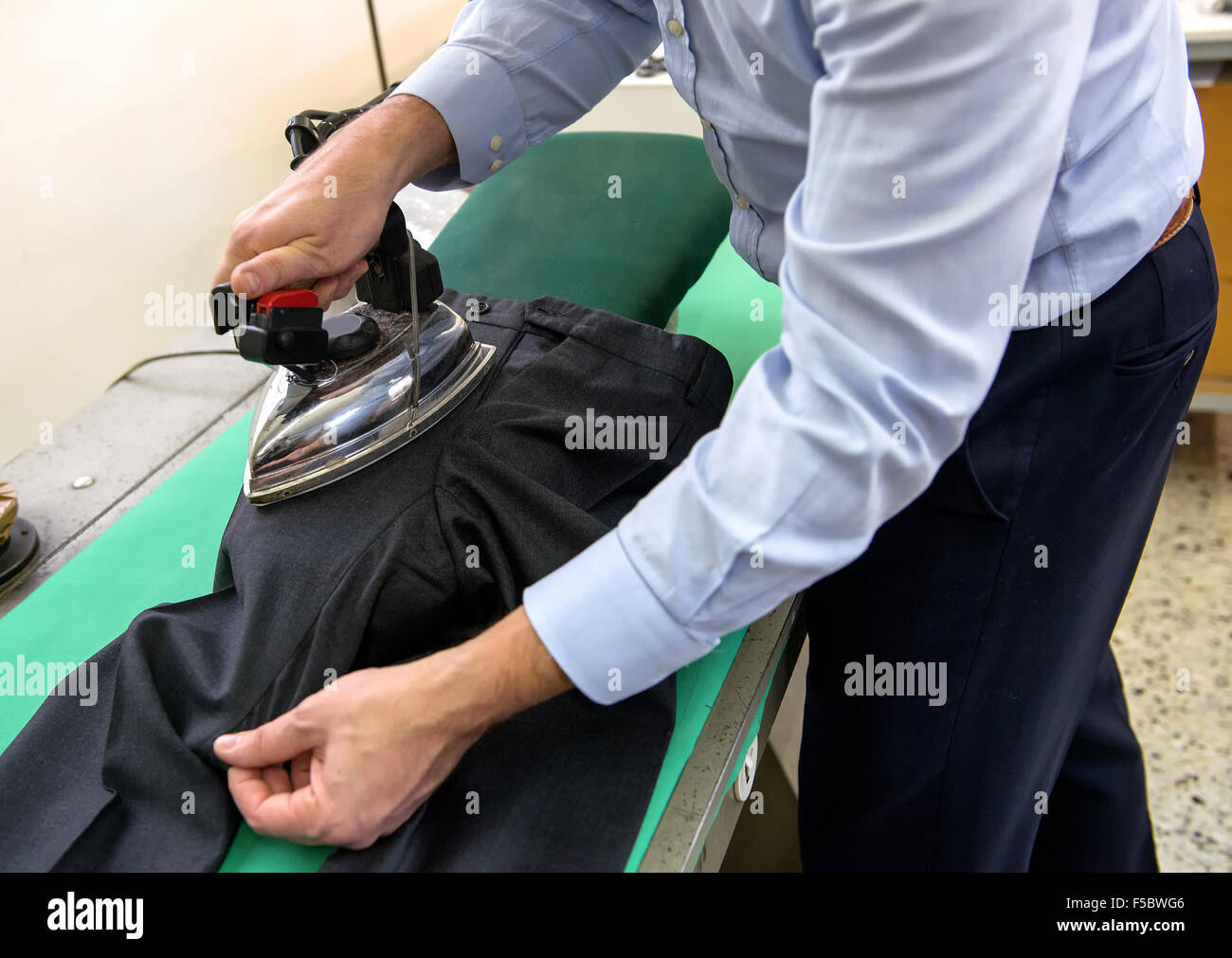 Tailor ironing black pants in a workshop - Stock Image