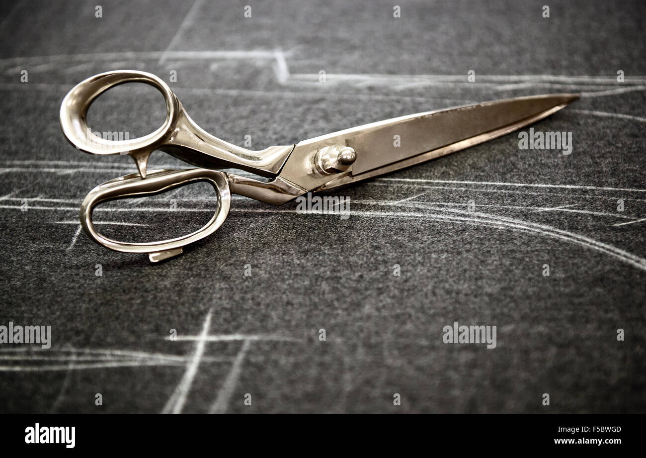 Tailors scissors lying on fabric marked in chalk - Stock Image