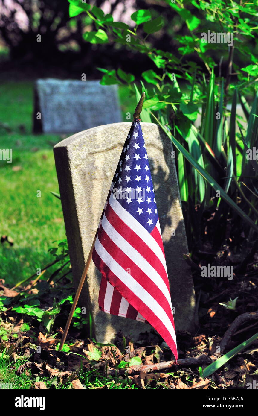 A grave marker, long ago made unreadable by the ravages of time, is adorned with an American Flag for the Fourth - Stock Image