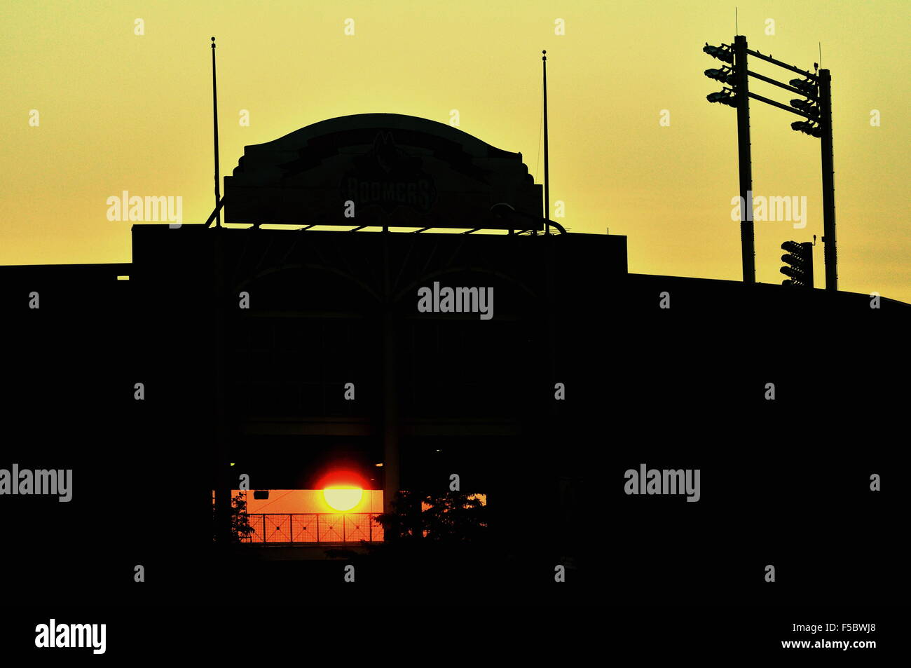 The sun rise shines through an empty Minor League Baseball stadium long before the game later in the day. Illinois, - Stock Image