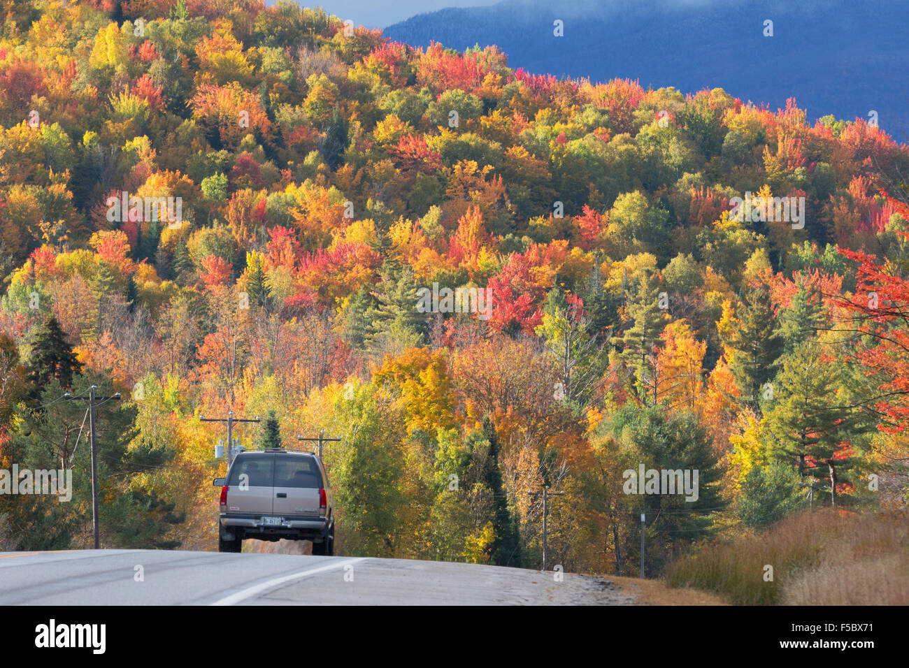A car driving along the Kancamagus Highway, route 112, in New England in autumn, with colourful foliage, White Mountains New Hampshire USA Stock Photo