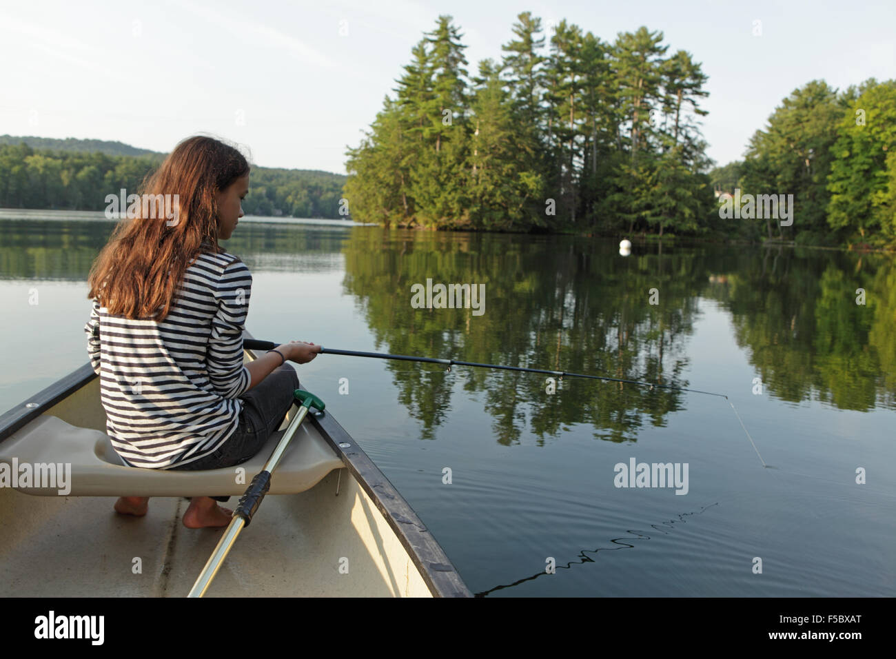 Young girl fishing from a canoe on a calm lake with trees in the background - Stock Image