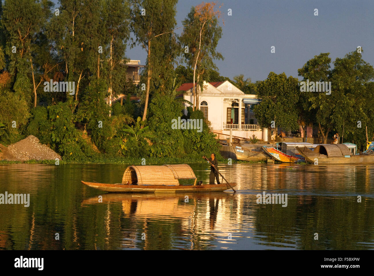 A wooden sampan makes its way up the brown waters of the Perfume River in Hue, Vietnam. - Stock Image
