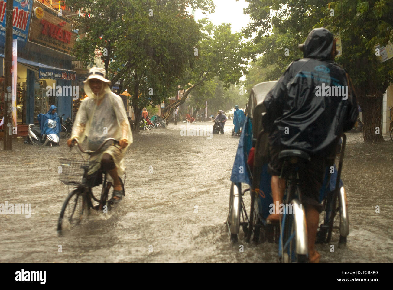 Monsoon rains in the city of Hue. People in tuc-tuc rides bicycle along flooded streets in Hue. Vietnam. - Stock Image