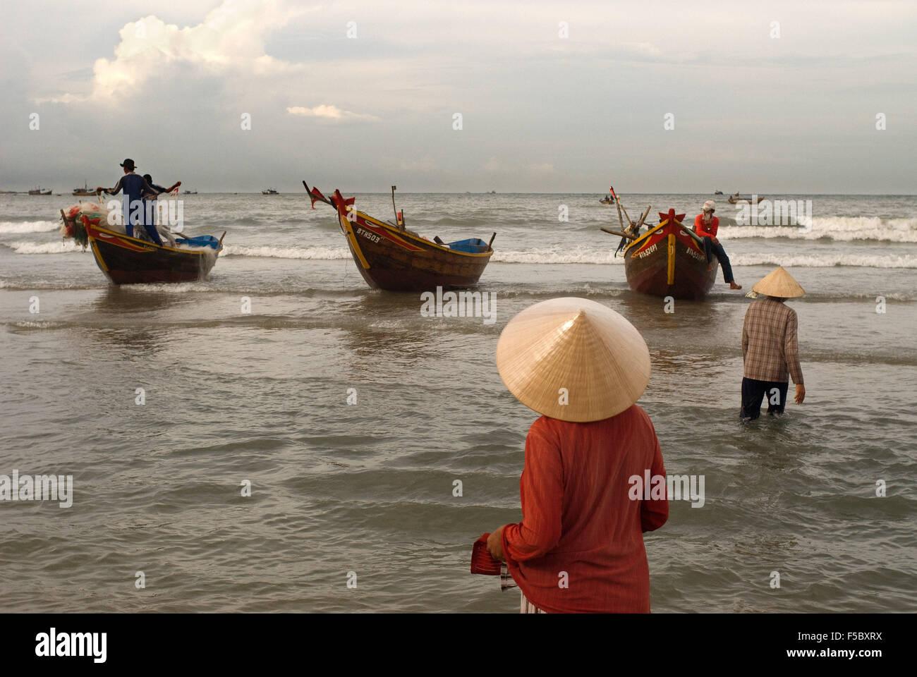 Lady awaiting the landing of the catch, Mui Ne fishing village, Bình Thuận Province, Vietnam - Stock Image