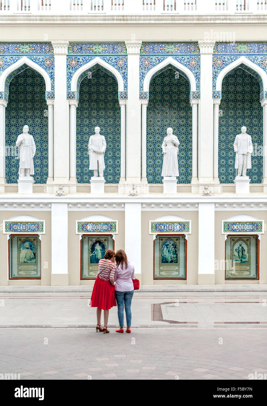 Two women standing in front of the Nizami Museum of Azerbaijan Literature in Baku. - Stock Image