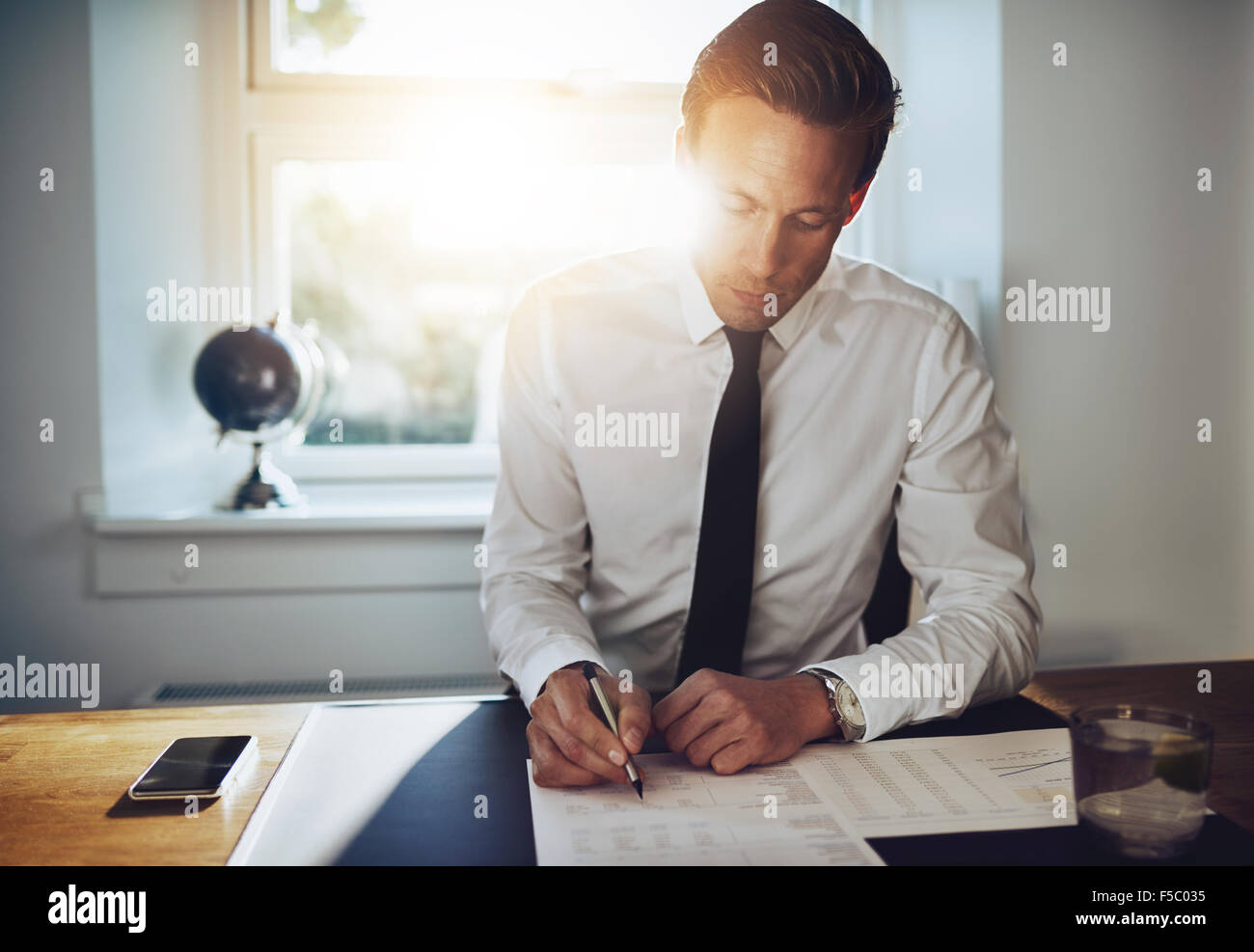 White business man signing a contract and looking at documents at his office while looking serious - Stock Image