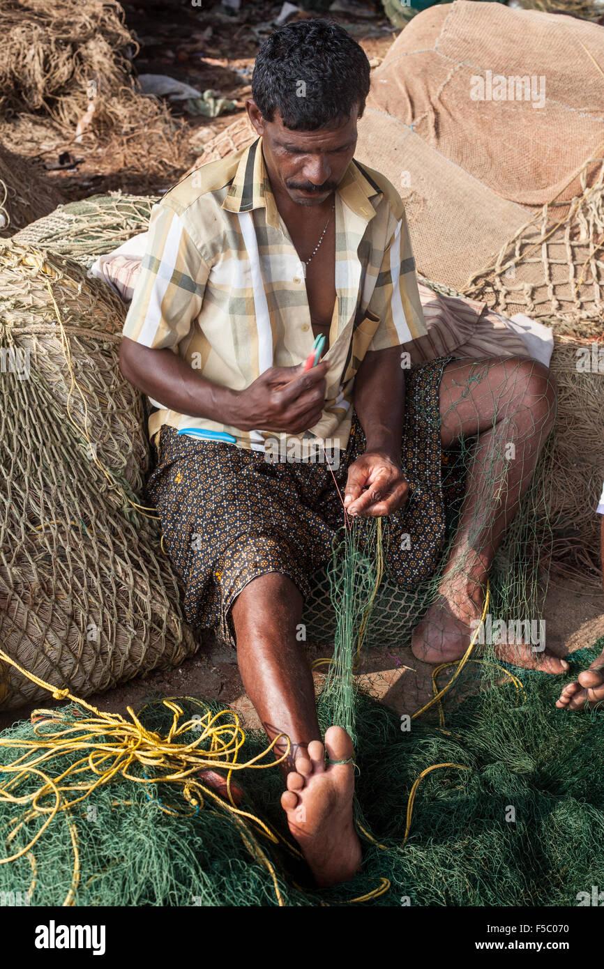 Vizhinjam Christian fisherman village in Kerala, India, November 2014. Fisherman repair their nets after their work. - Stock Image