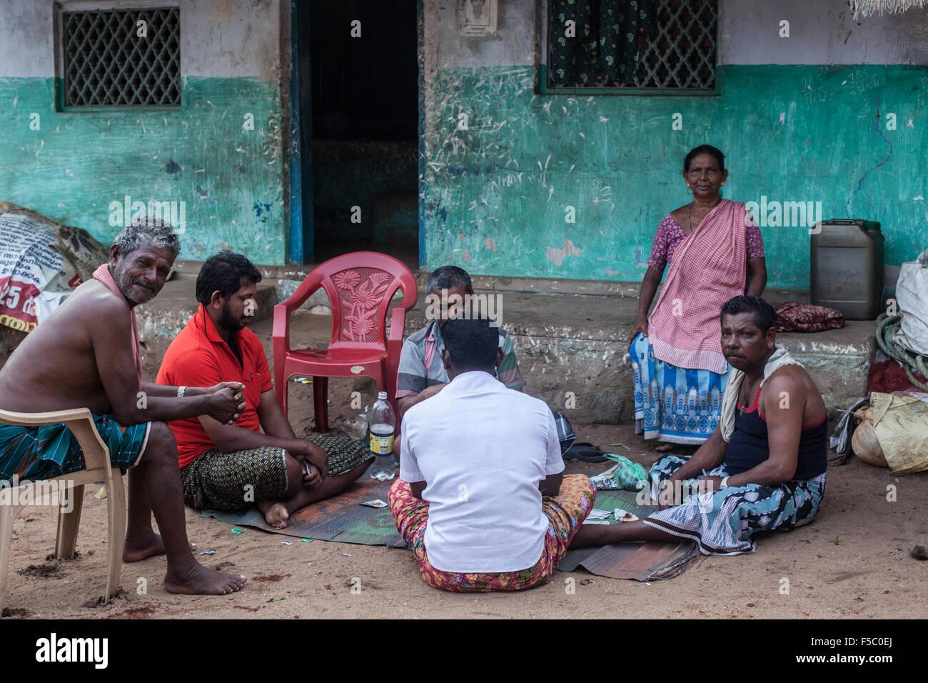 Vizhinjam Christian fisherman village in Kerala, India, November 2014. Fisherman relax with card game after hard - Stock Image