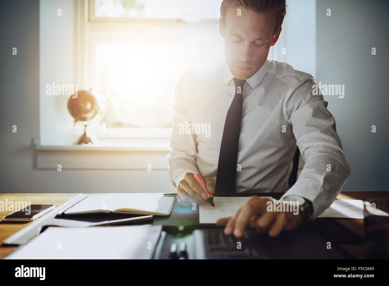 Executive business man working on accounts while being concentrated and serious, wearing white shirt and tie - Stock Image