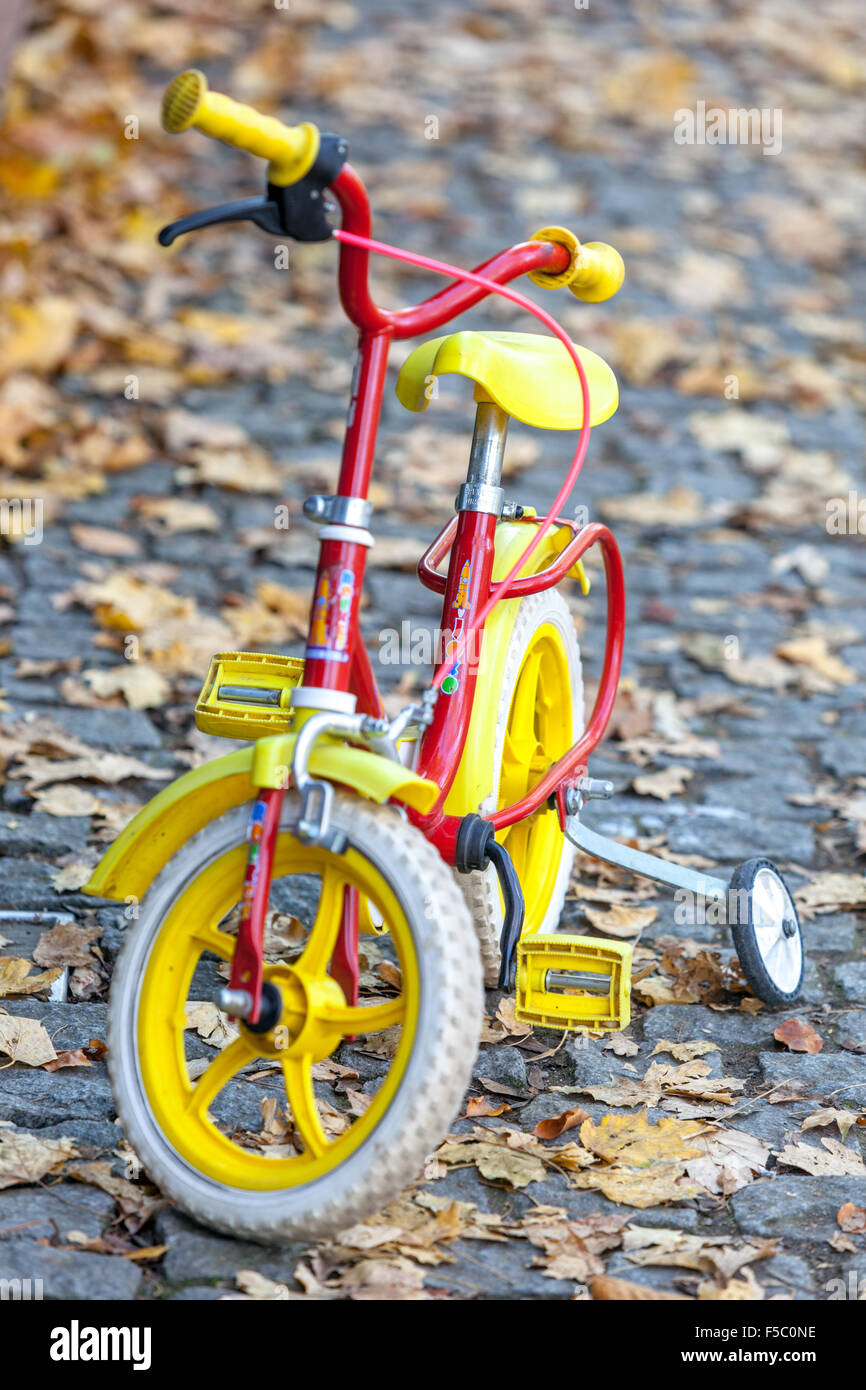 Baby bicycle with stabilizers, autumn fallen leaves on street, Prague - Stock Image