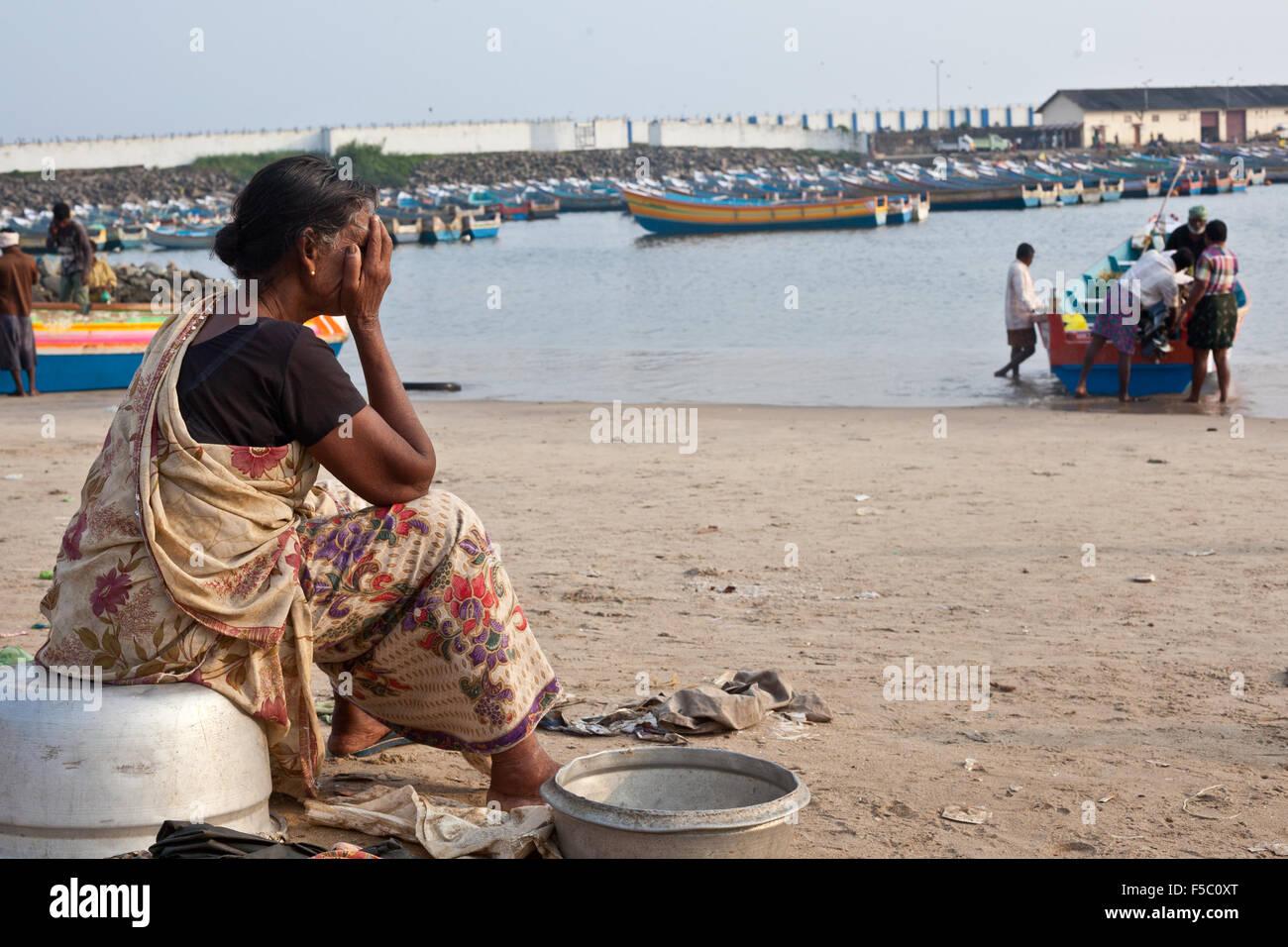 Vizhinjam Christian fisherman village in Kerala, India, November 2014. Women wait for fisherman boats. - Stock Image