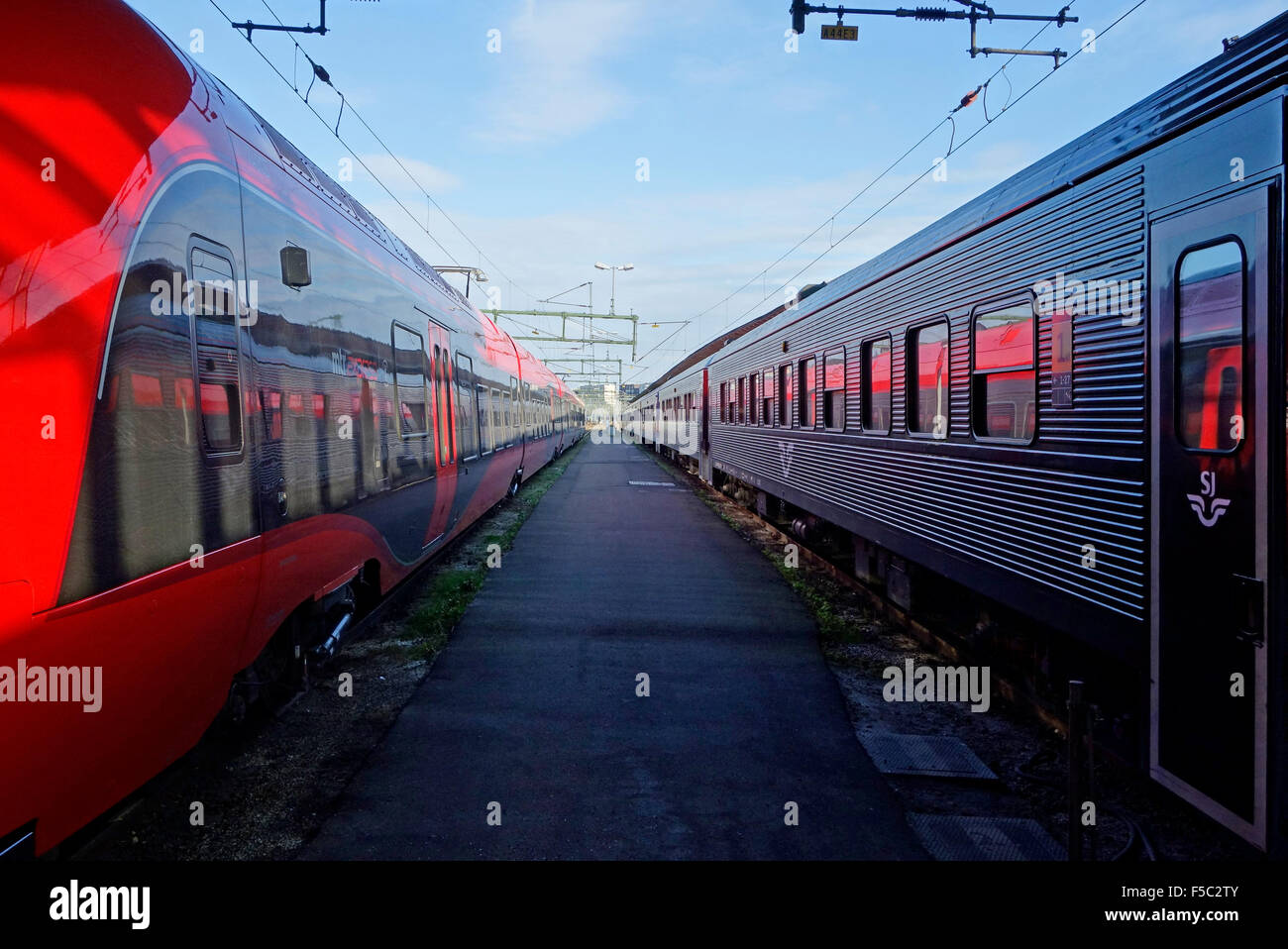 Two railway trains on each side of an empty platform in Central station in Göthenburg, Sweden - Stock Image
