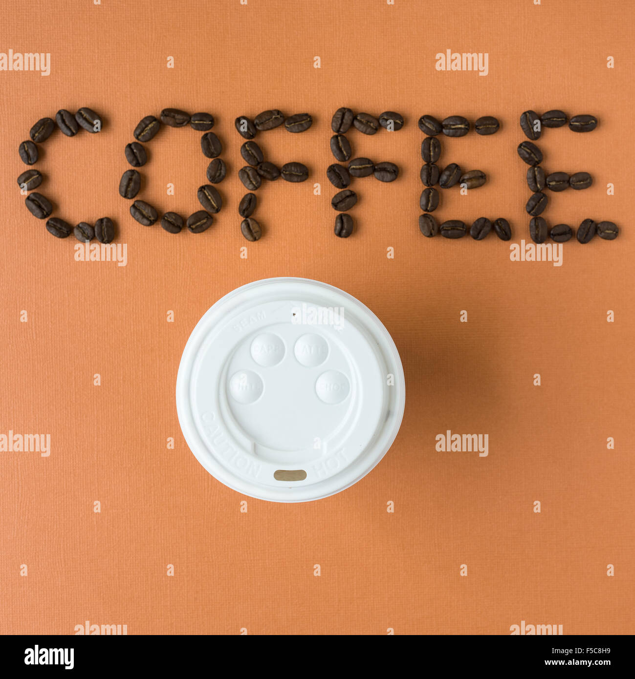 coffee spelled out with roasted coffee beans, on orange background Stock Photo