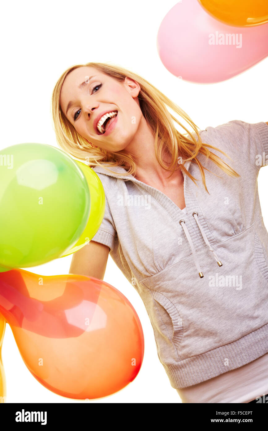 Junge blonde Frau hält lachend viele Luftballons Stock Photo