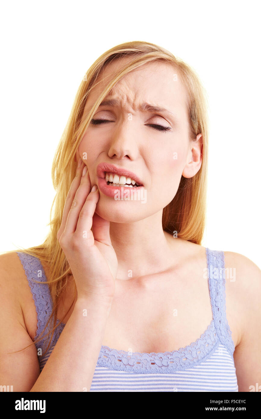 Young blonde woman with toothache holding her cheek - Stock Image