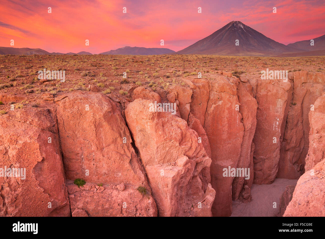 A narrow canyon with a volcano in the distance. Photographed at the foot of Volcan Licancabur in the Atacama Desert, - Stock Image