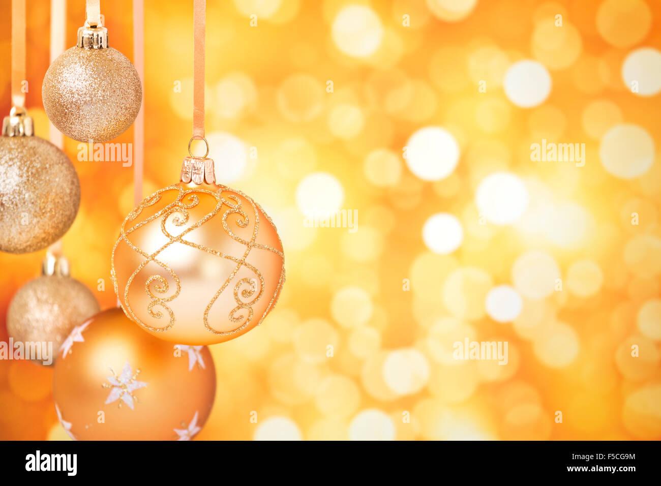 Golden Christmas baubles hanging in front of defocused golden lights. Stock Photo