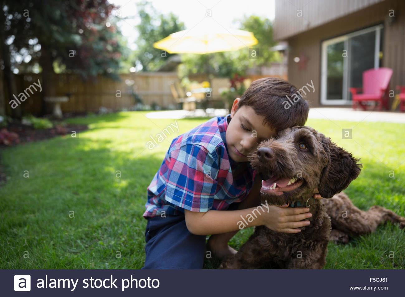 Affectionate boy hugging dog on lawn - Stock Image