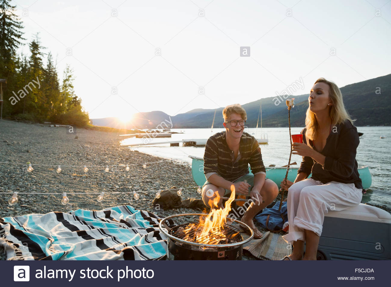 Young couple roasting marshmallows at lakeside campfire - Stock Image
