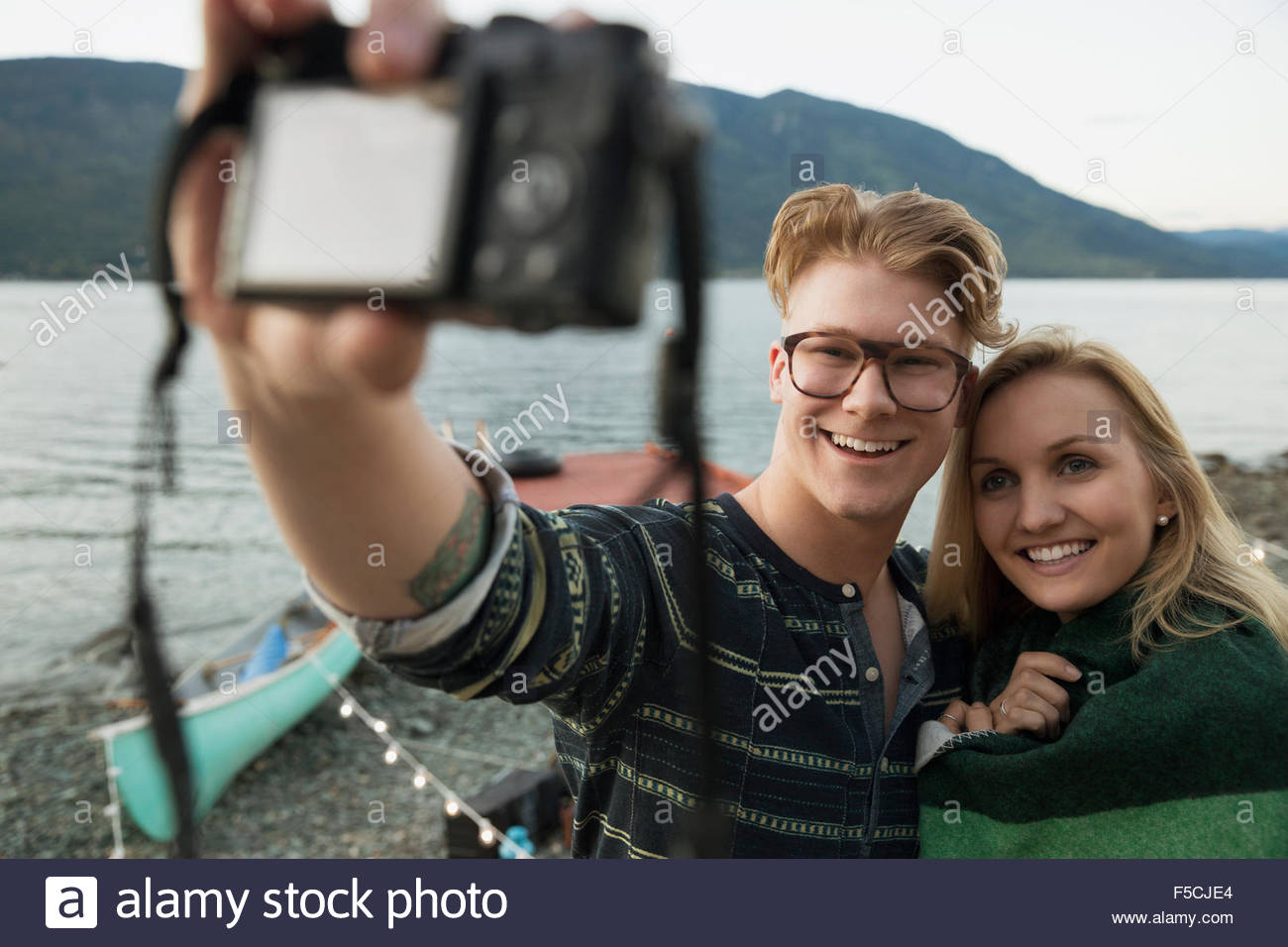 Smiling young woman wrapped in a blanket lakeside - Stock Image