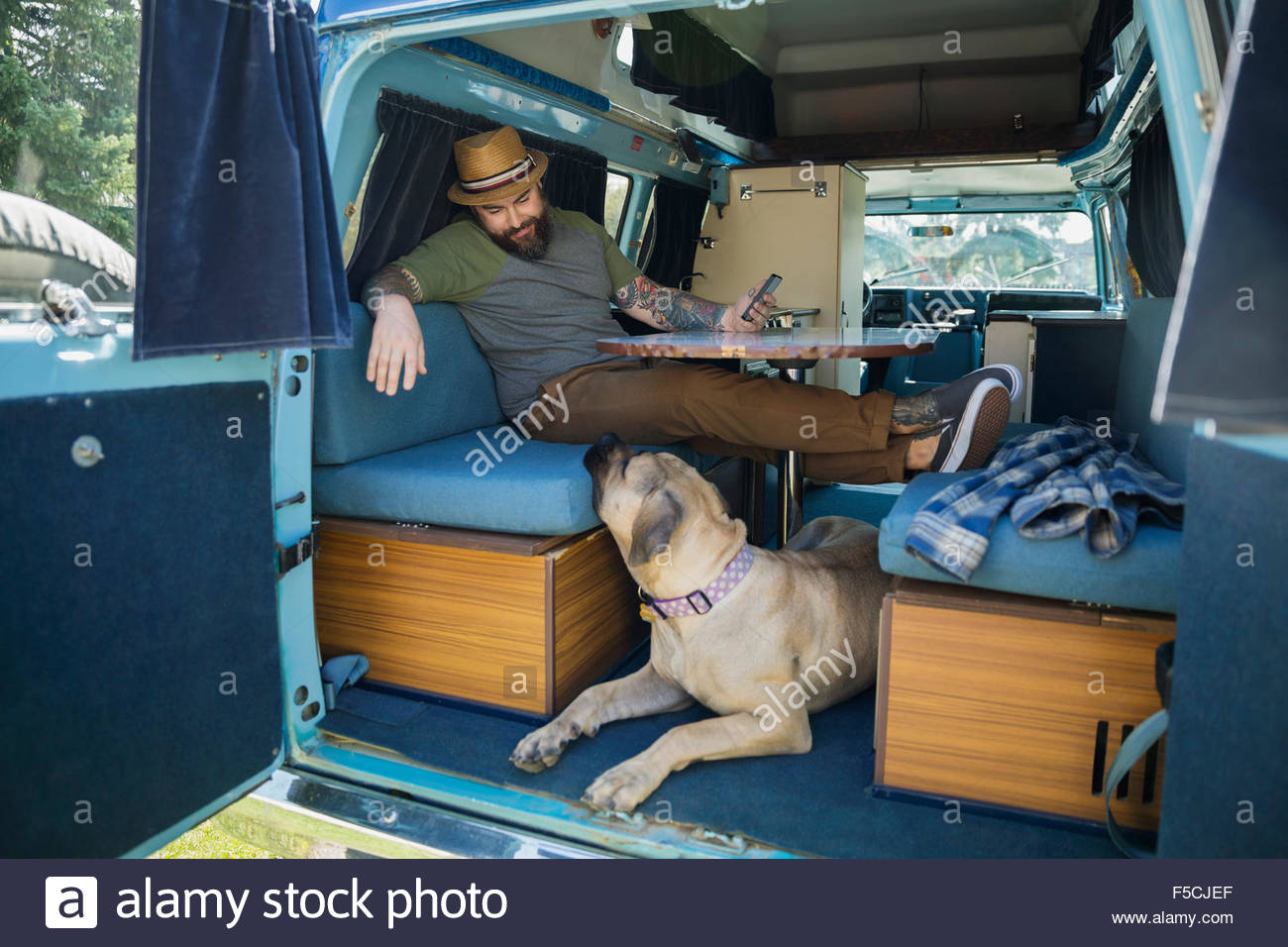 Man relaxing with dog in camper van stock image