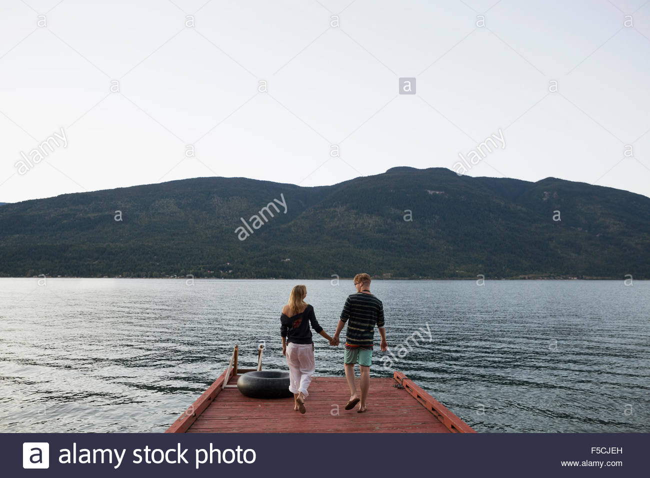 Young couple holding hands walking on lake dock - Stock Image