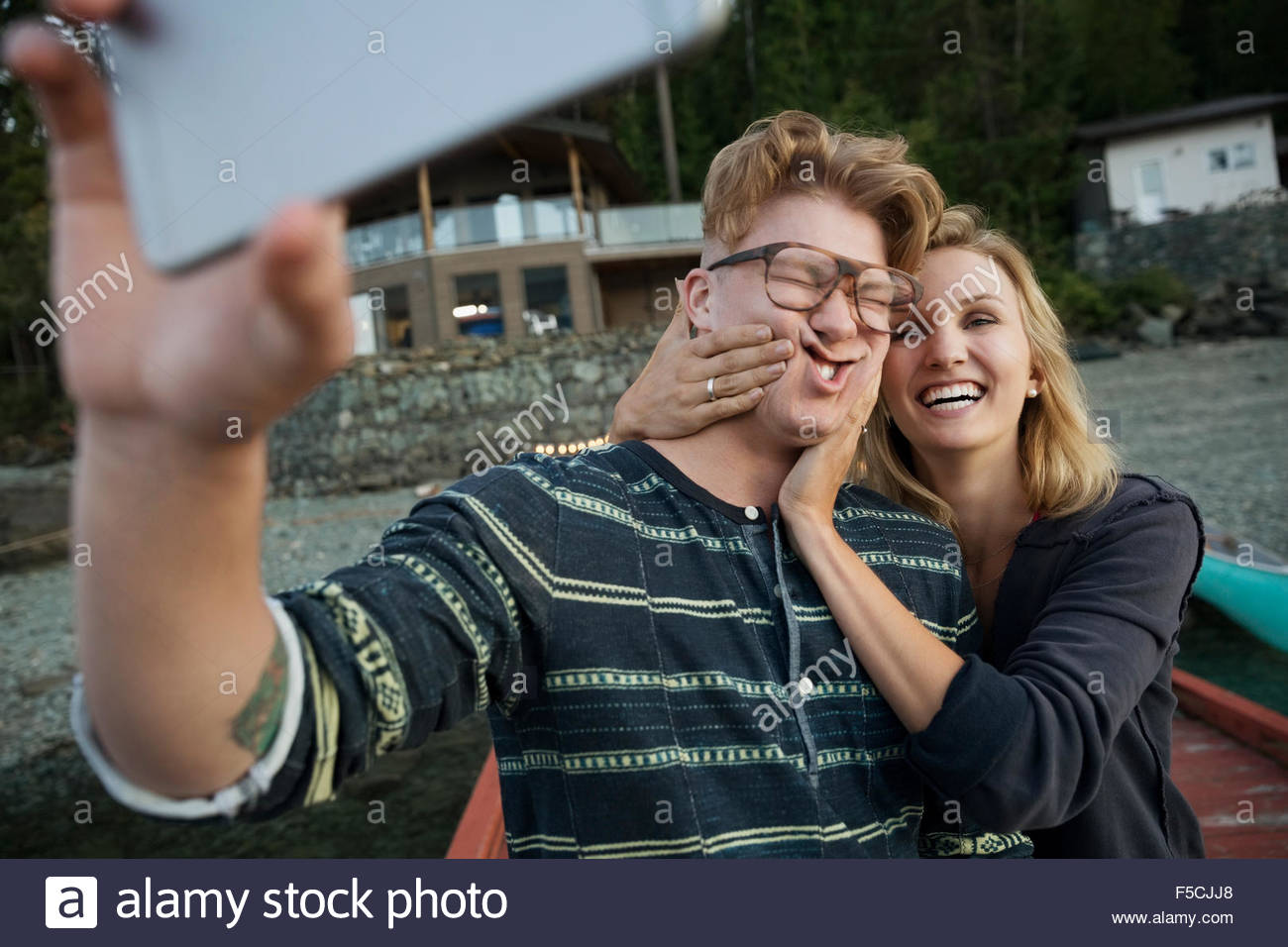 Playful couple making a face taking selfie - Stock Image
