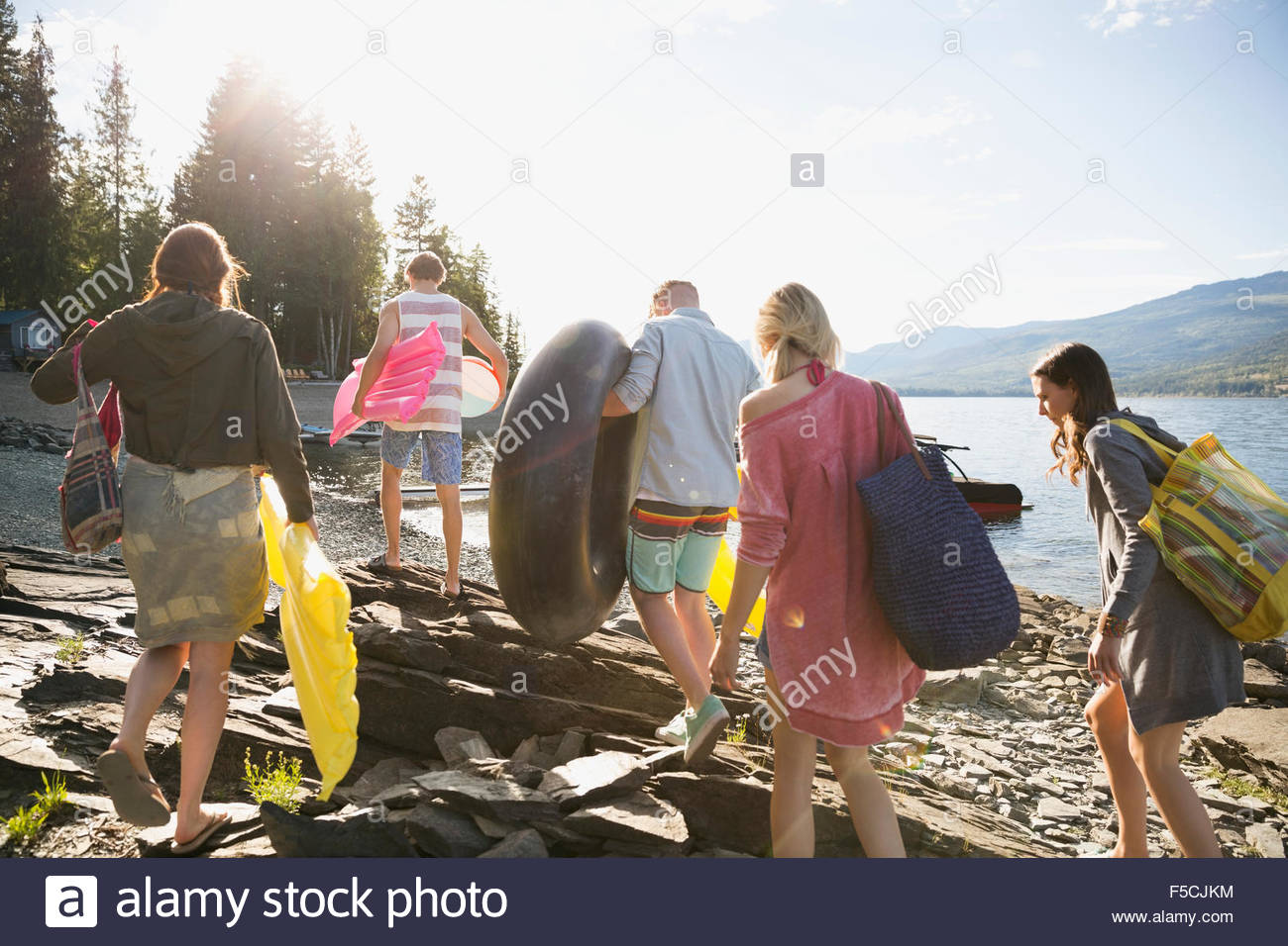 Young friends carrying pool rafts at sunny lakeside Stock Photo