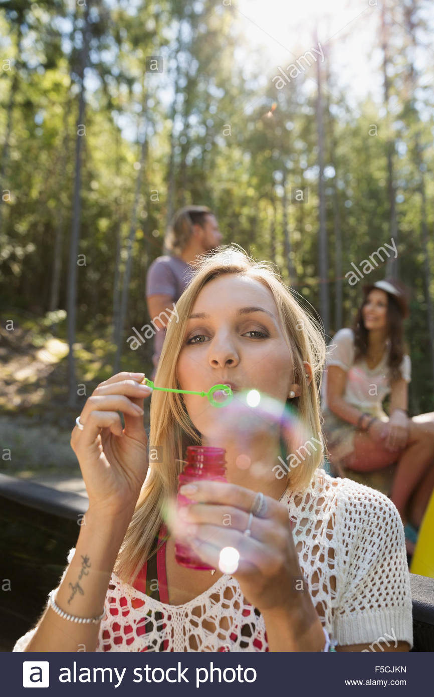 Portrait young woman blowing bubbles - Stock Image