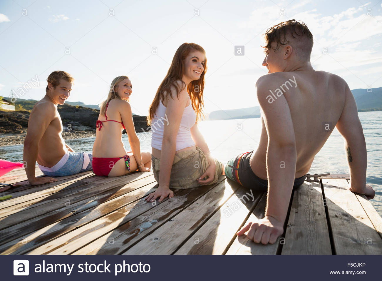 Young friends hanging out on sunny lake dock - Stock Image
