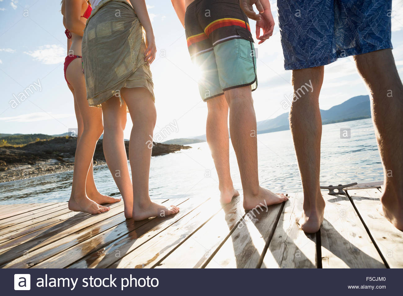 Young friends standing on sunny lake dock - Stock Image