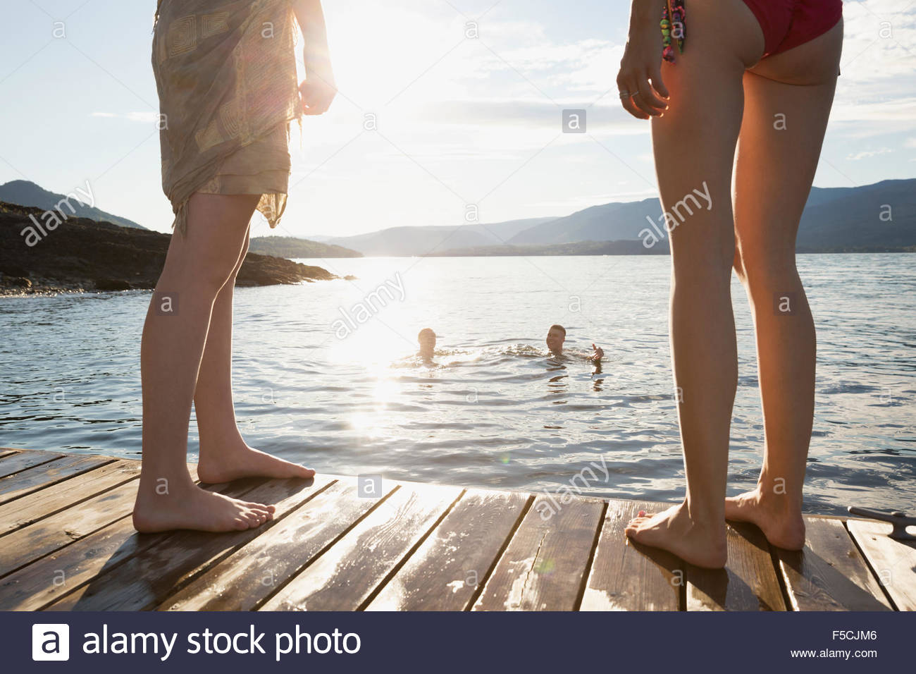 Women on dock watching men swimming in lake - Stock Image