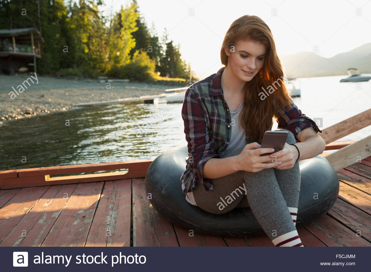 Young woman texting on lake dock Stock Photo
