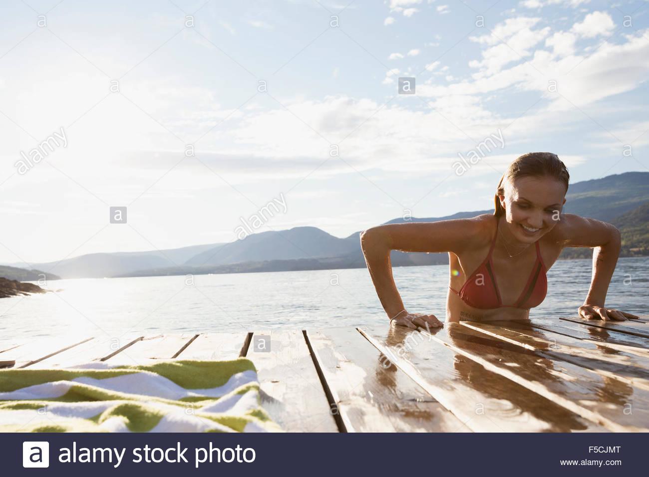 Young woman climbing onto lake dock - Stock Image