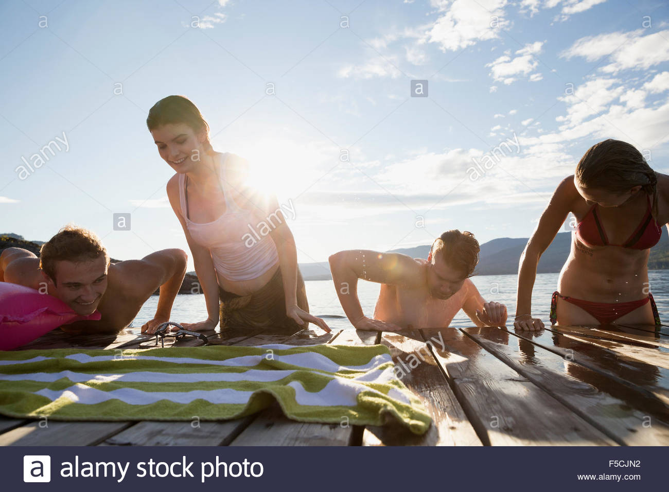 Young friends climbing onto lake dock - Stock Image