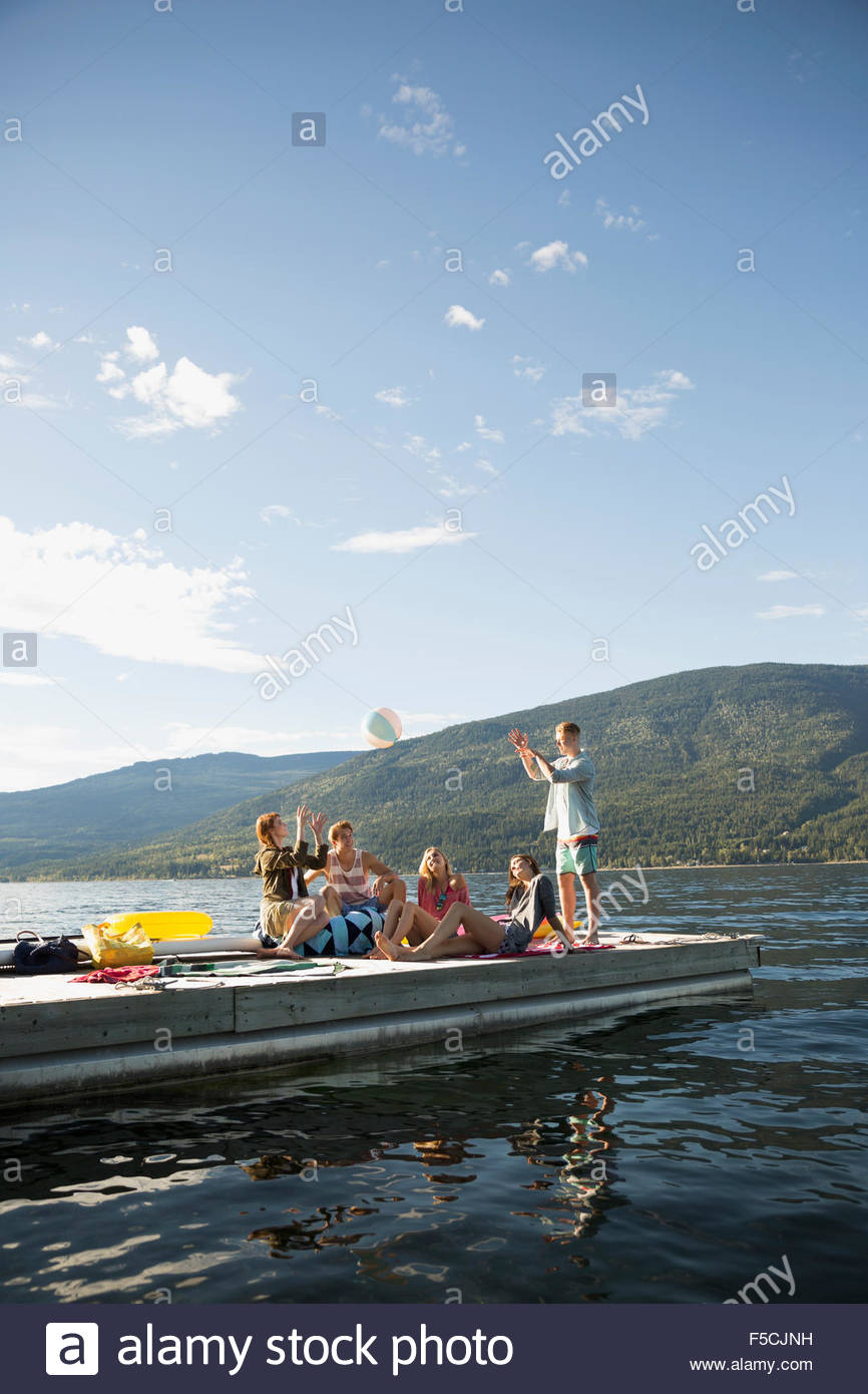 Young friends hanging out at sunny lake dock - Stock Image