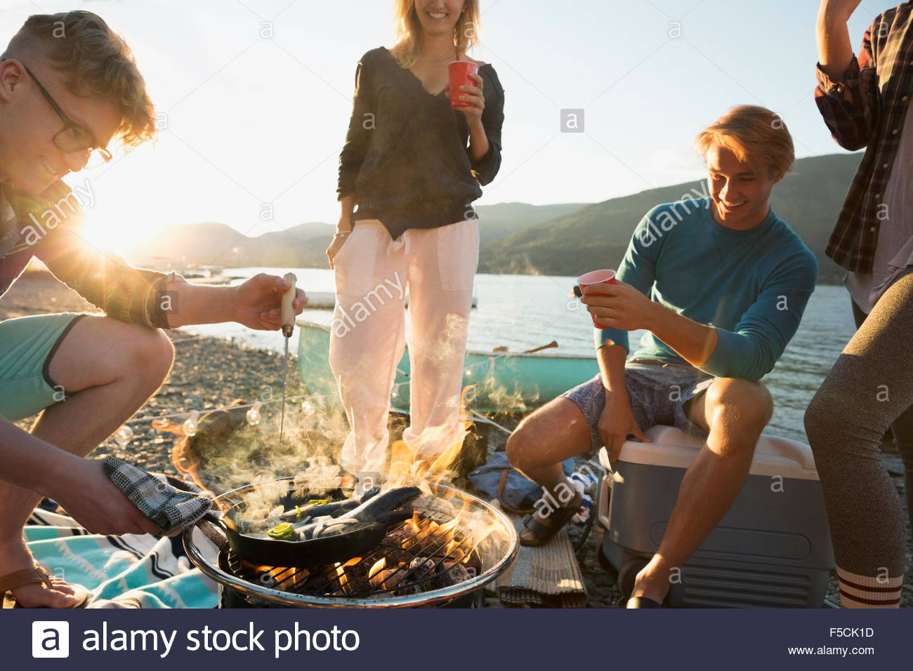 Young friends cooking at lakeside campfire - Stock Image