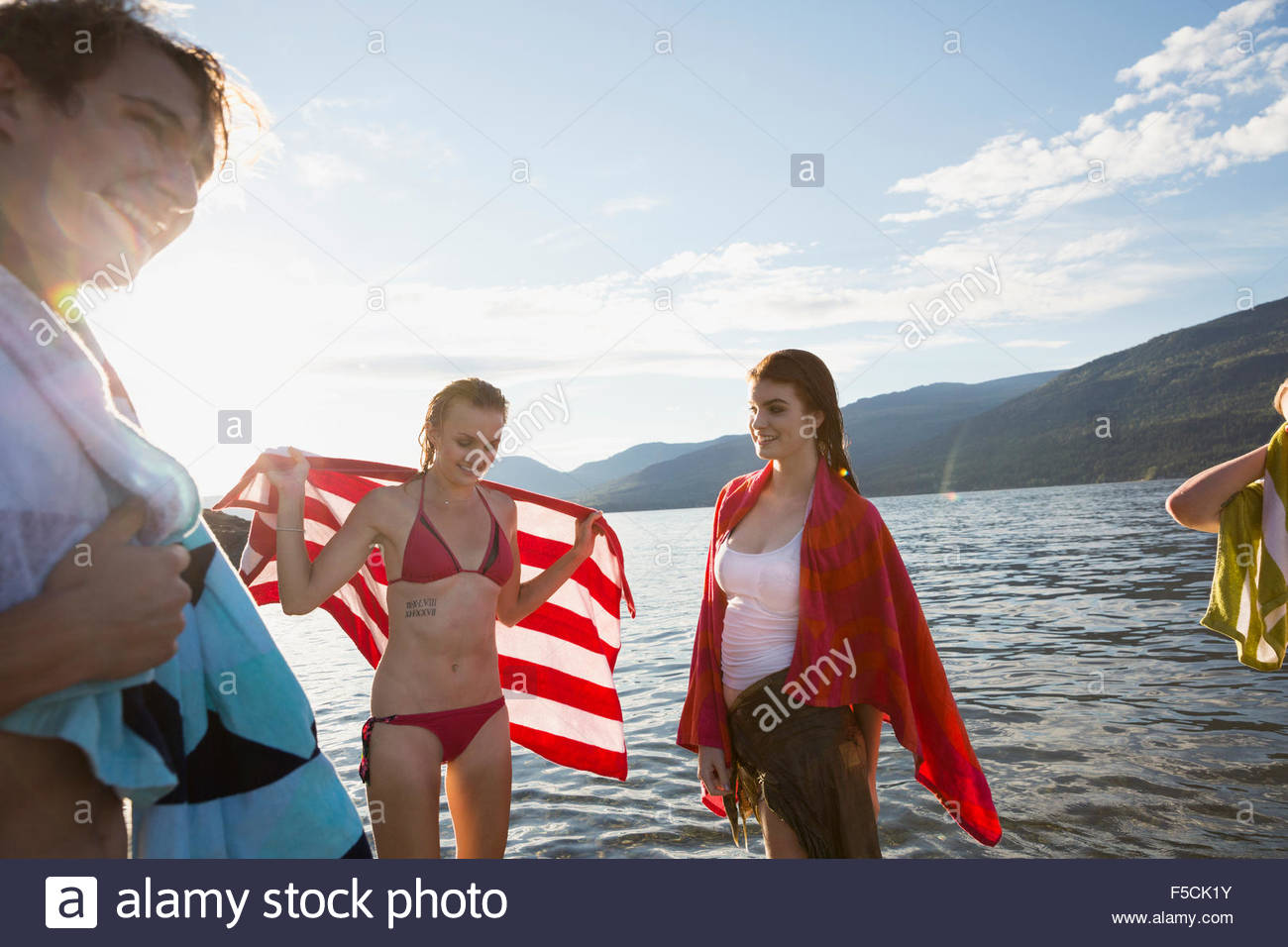 Young friends drying off at lake - Stock Image