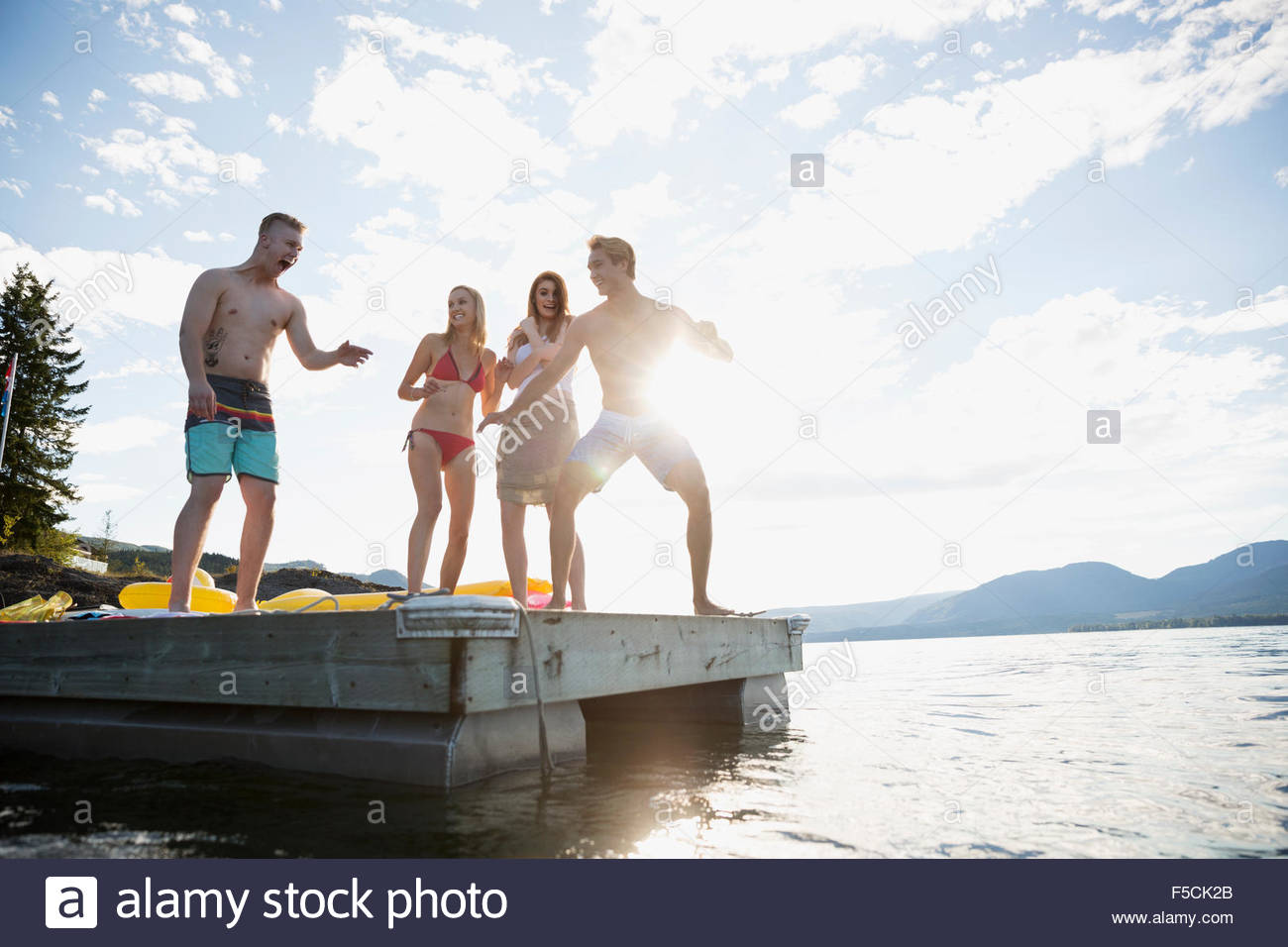 Playful young friends on sunny lake dock - Stock Image