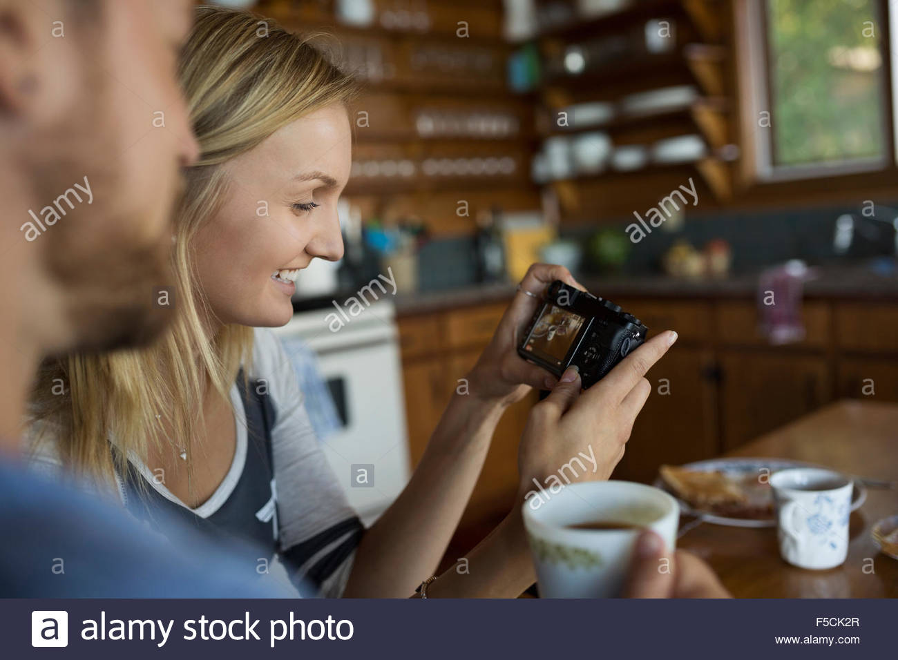 Young couple viewing digital camera in kitchen - Stock Image