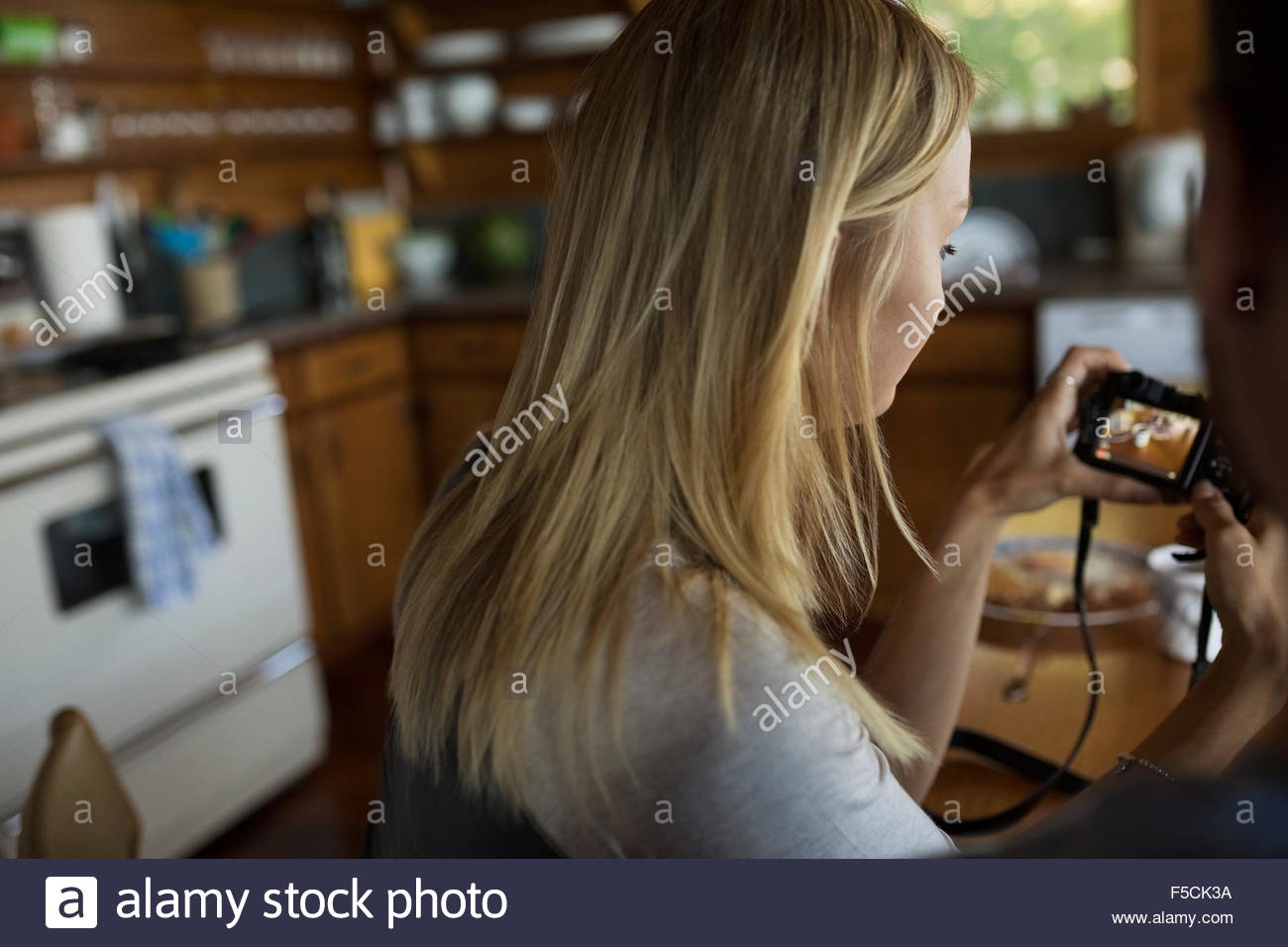 Young woman viewing digital camera in kitchen - Stock Image